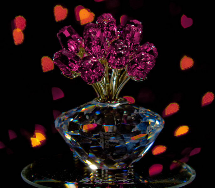 Bouquet with Bokeh (5/11/2010)<br /> <br /> A local photography meetup group I attend suggested a simple theme for this months meeting of bokeh.  This is my first attempt at a custom bokeh, I like how the bokeh turn out like diamonds, hearts, and petals.  The bouquet is a signed Swarovski Crystal 2002 Jubilee Edition Vase of Roses.  The real bouquet was a lot harder to photograph than I thought it would be.<br /> <br /> Hope you have a great Tuesday and thanks for all the great comments on the rose yesterday.<br /> -Bob